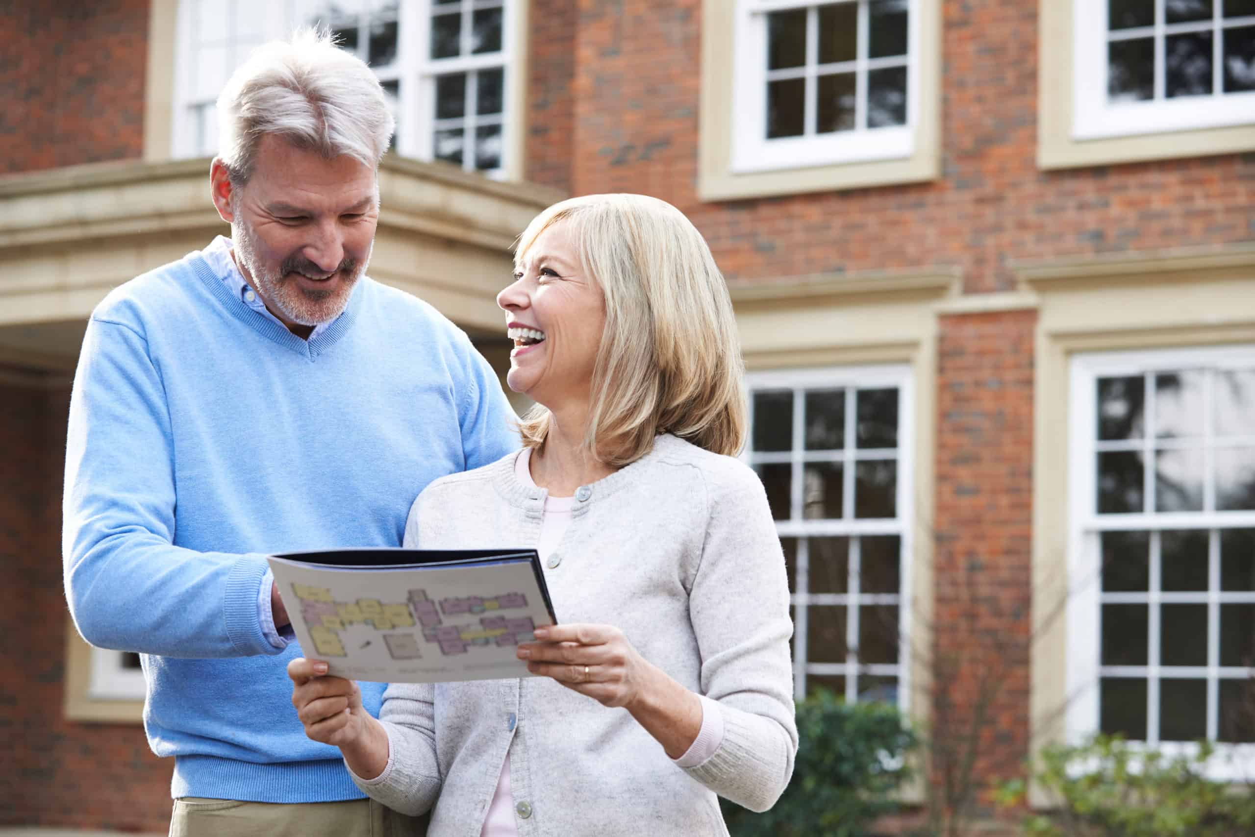 Couple Standing Outside House Looking At Property Details