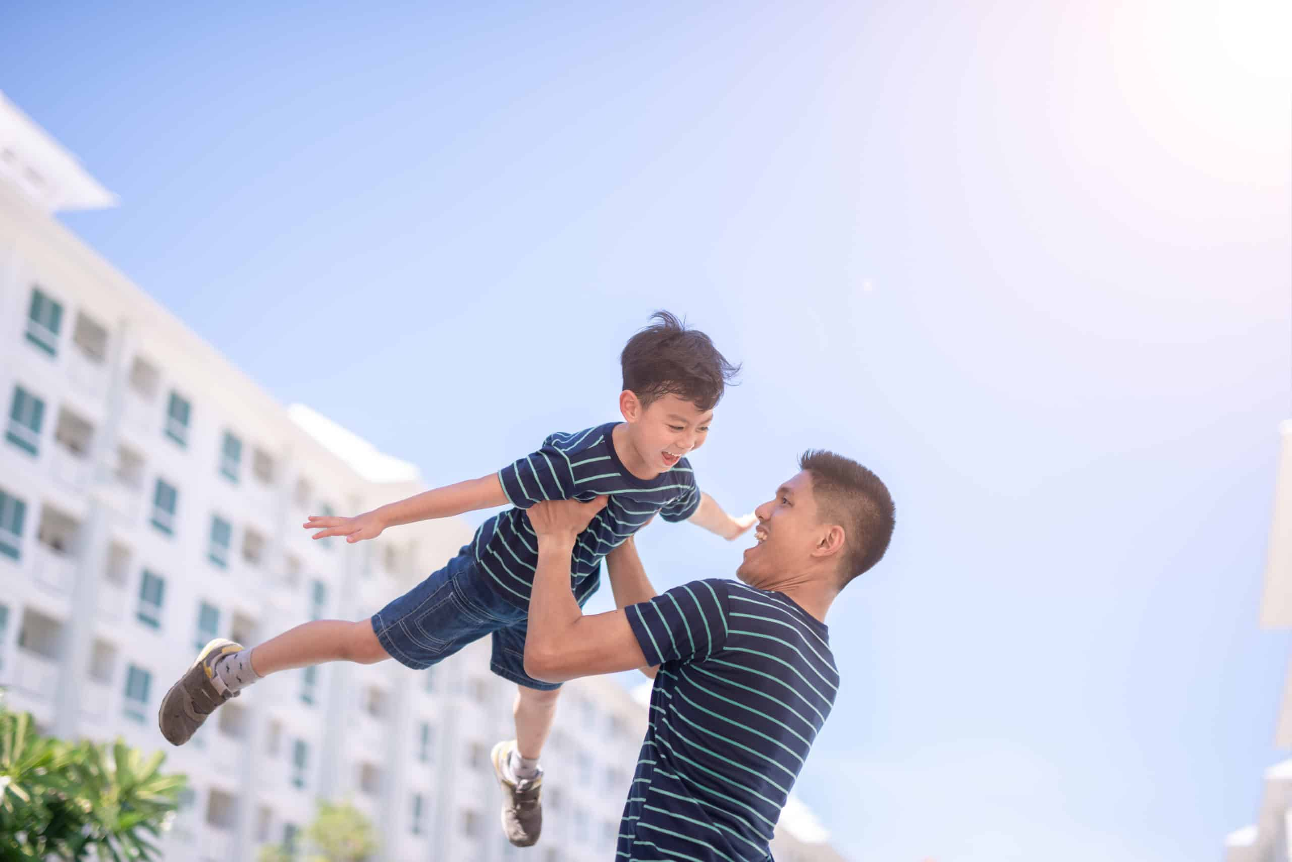 Happy father and son playing outside an apartment.
