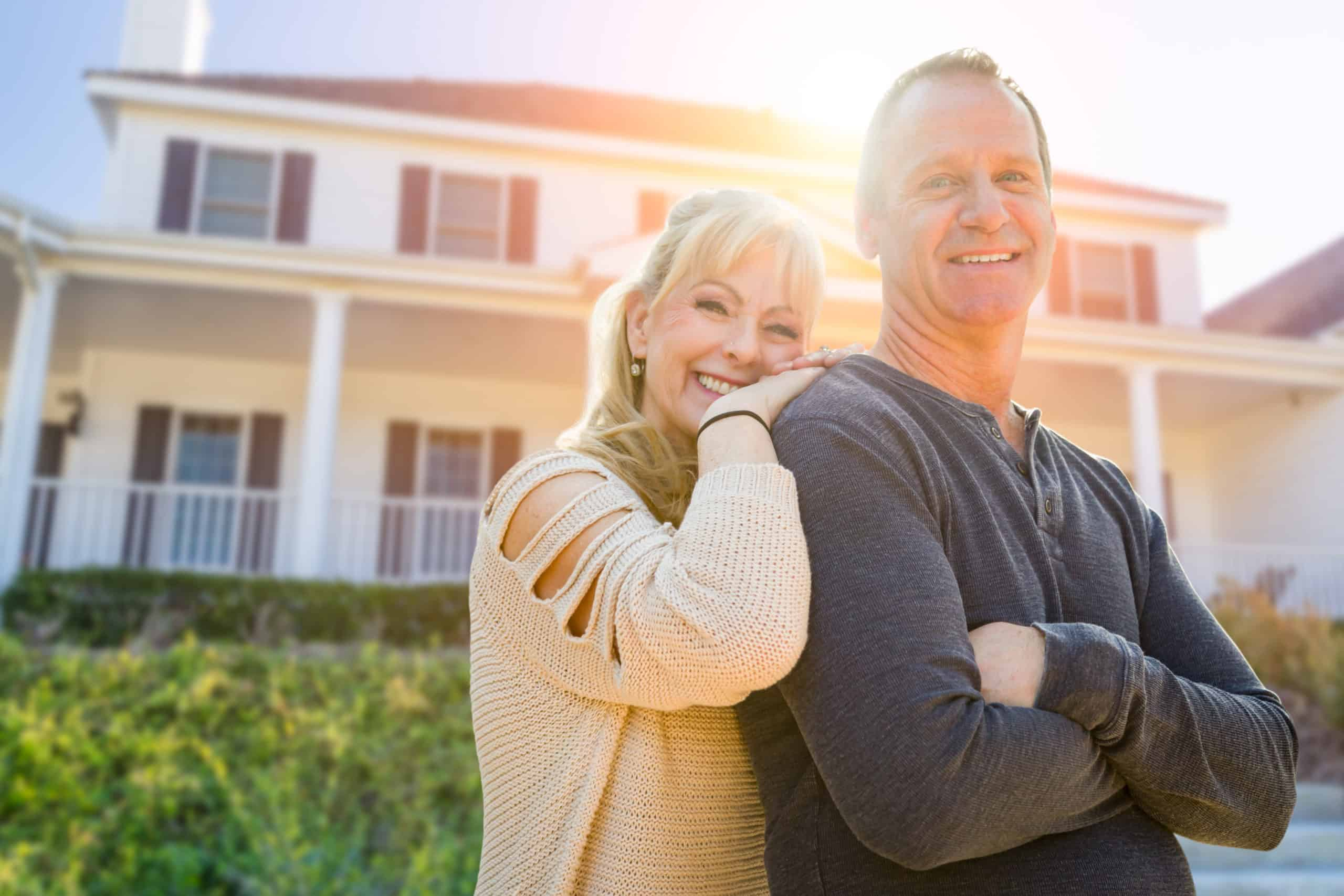 Middle-aged Couple In Front Of Their House.