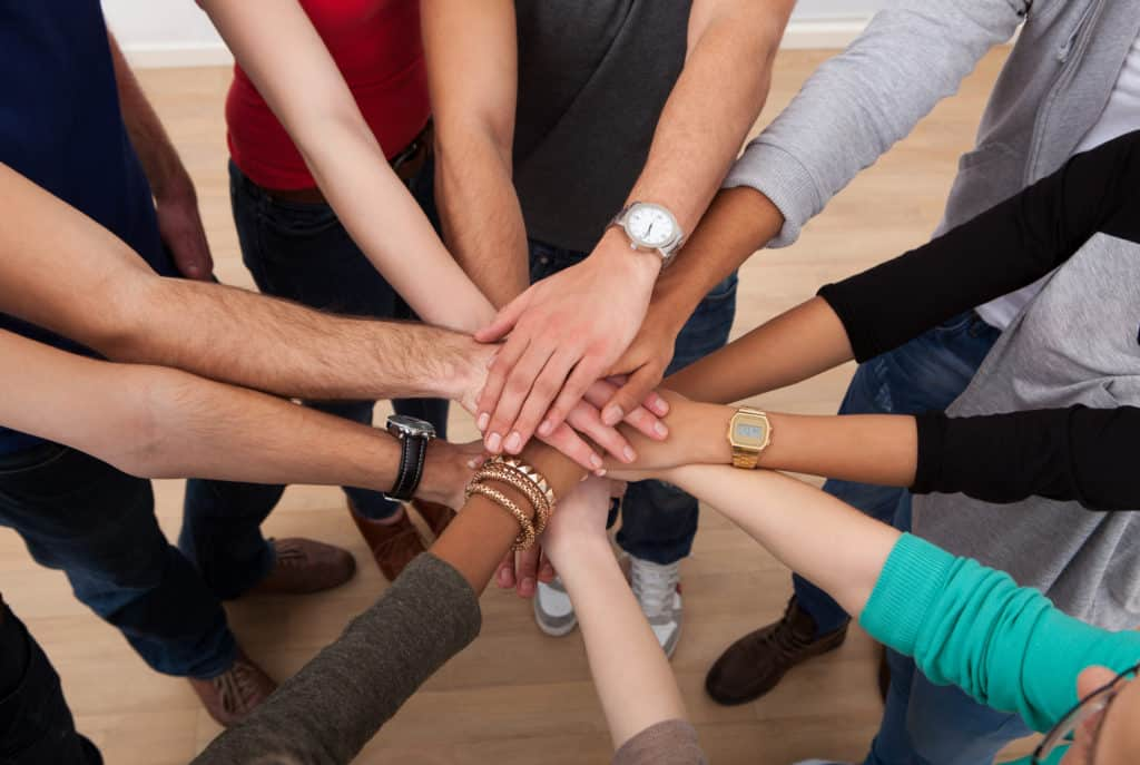 High angle view of community stacking hands together