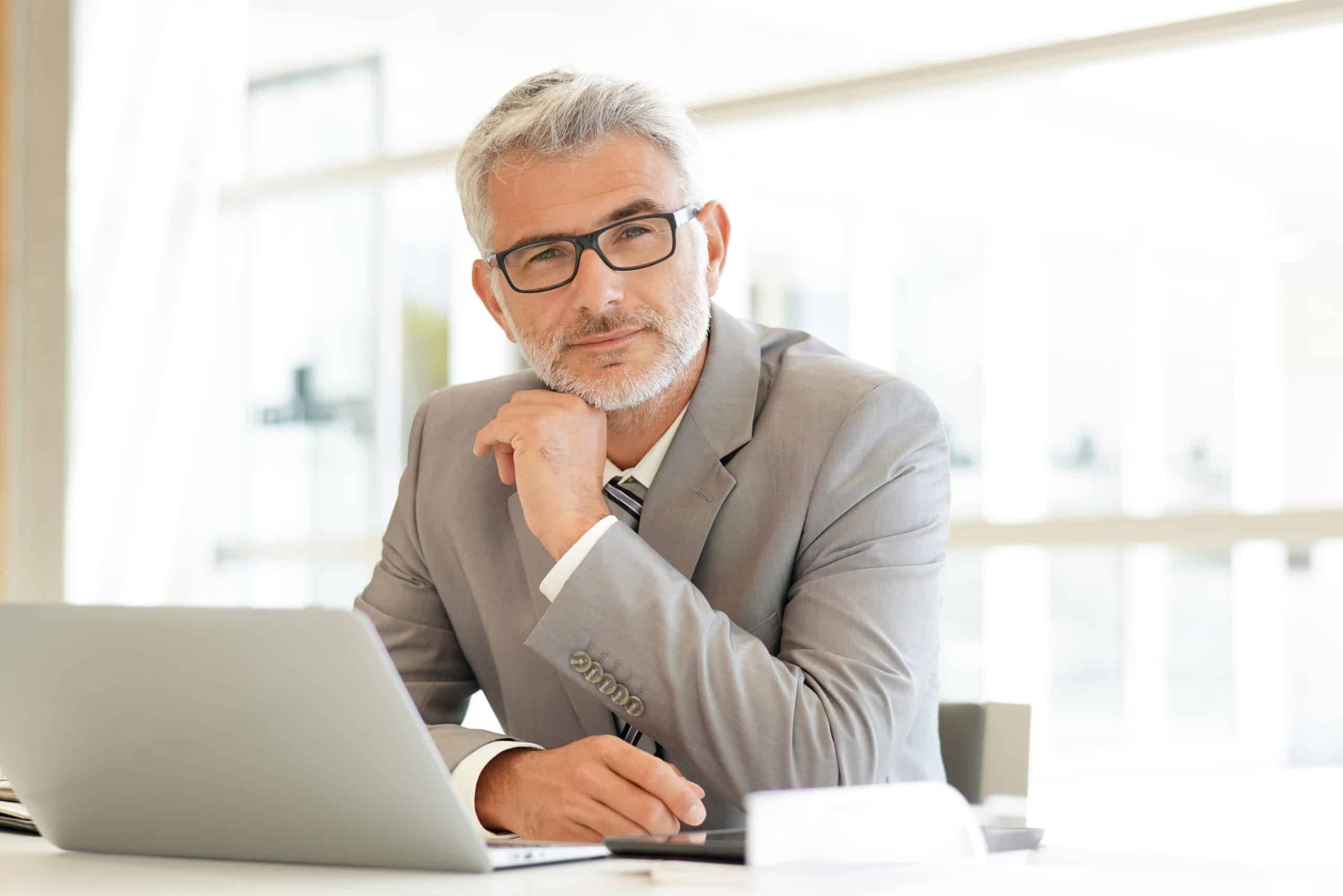 Mature businessman sitting at desk looking at camera