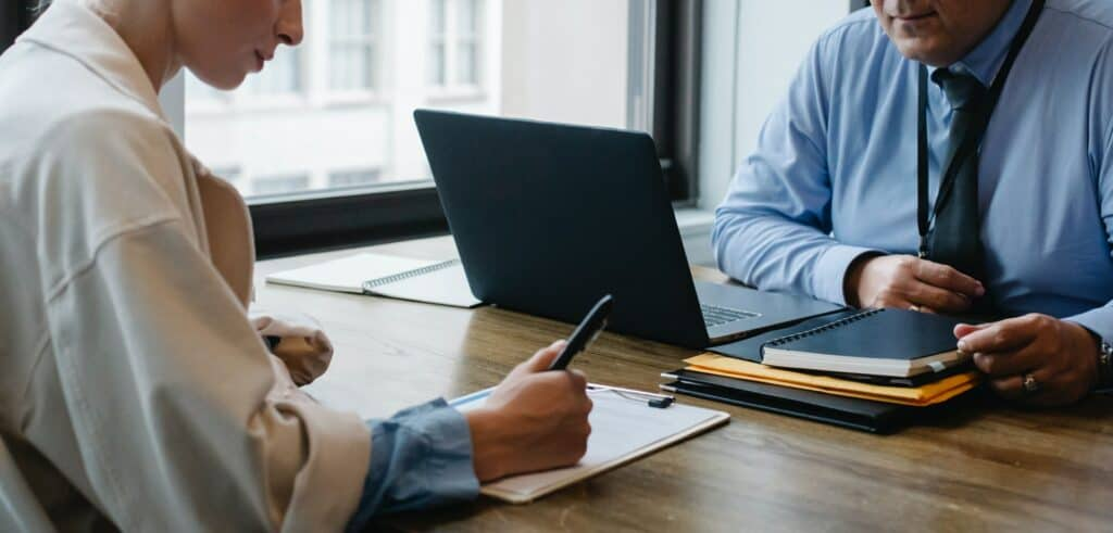 Cropped Business Partners Signing Papers in Office